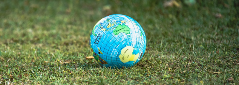 Green grass with world globe ball on it showing australia and antarctica
